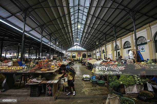 Vendors sell vegetables near a ruling Frelimo party flag and of the main opposition party Renamo inside the Maputo Central Market in the Mozambican...