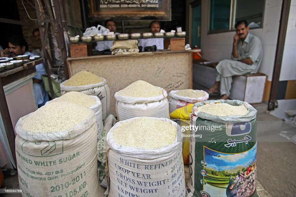 Vendors sit behind sacks of rice for sale at a market in the district of Faisalabad in Punjab, Pakistan, on Sunday, Oct. 13, 2013. Prime Minister Nawaz Sharifs four-month-old government is struggling to revive the $231 billion economy crippled by chronic energy shortages and a spike in violence from a Taliban insurgency in the northwest. Photographer: Asad Zaidi/Bloomberg via Getty Images