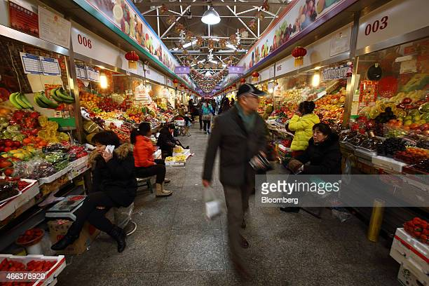 Vendors sit beside their fruit stalls at a market in Beijing China on Wednesday March 4 2015 China's leaders are gathered this week in Beijing where...