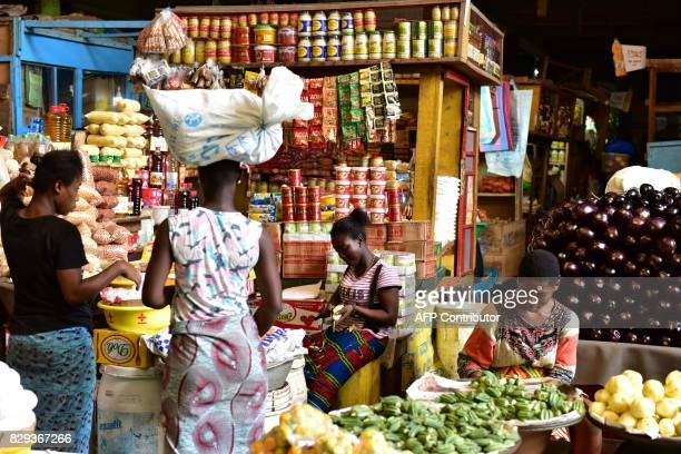 Vendors sit in front of stalls with various consumer products at the large market of Adjame a popular district of Abidjan on August 10 2017 The...