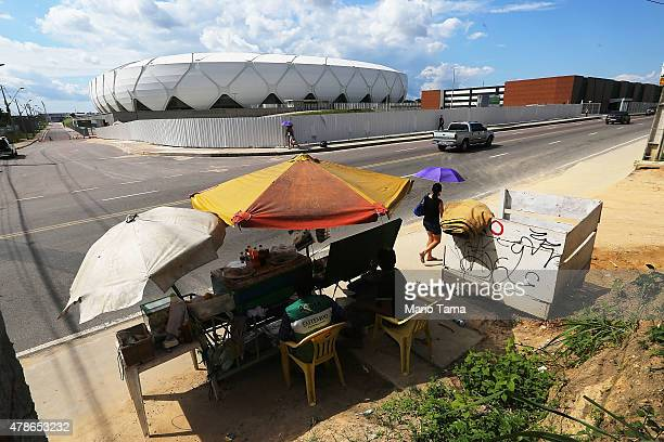 Vendors sit in front of the Arena de Amazonia June 26 2015 in Manaus Brazil The arena was constructed for $300 million as one of the host sites for...