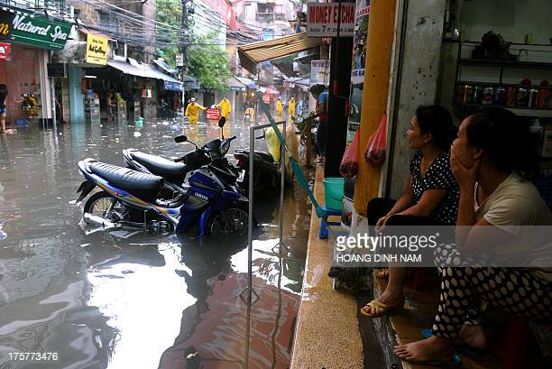 Vendors sit looking out at a flooded street in the old tourist quarter following heavy rains on August 8 2013 in downtown Hanoi A typhoon that hit...