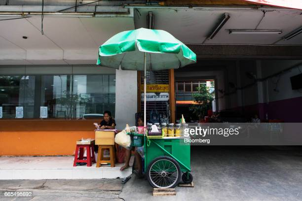 Vendors sit next to a street cart selling desserts in the Phaya Thai District of Bangkok Thailand on Wednesday April 5 2017 The central...