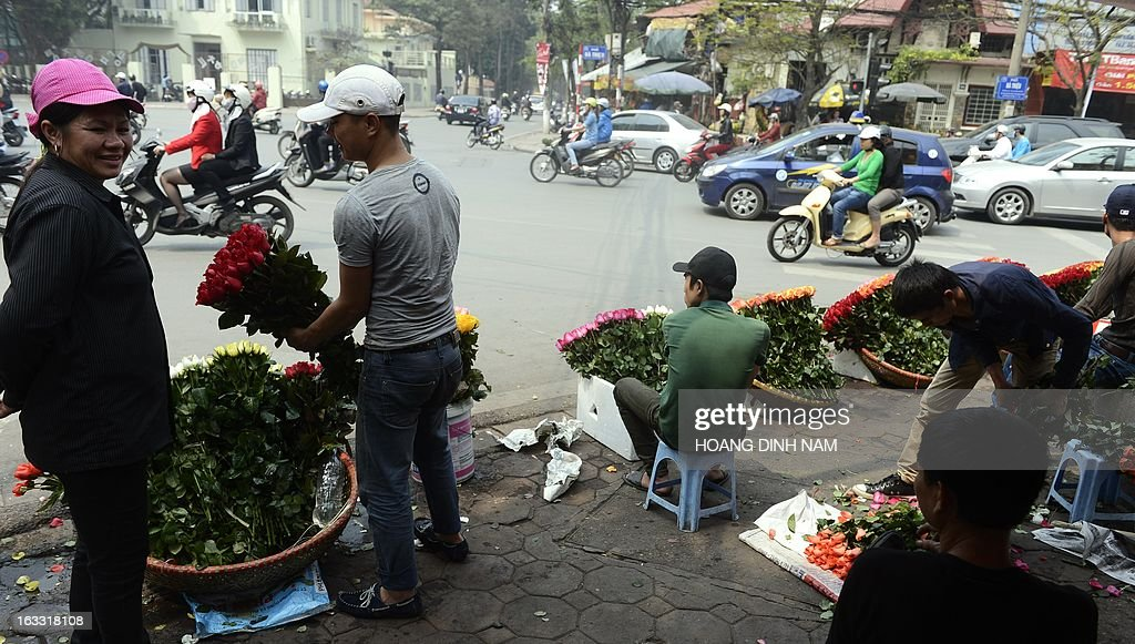 Vendors sit selling roses at a street corner as Vietnamese celebrate the International Women's Day in Hanoi on March 8, 2013. The day is a good business opportunity for florists with a sharp rise of flowers's prices, especially for roses. AFP PHOTO/HOANG DINH Nam