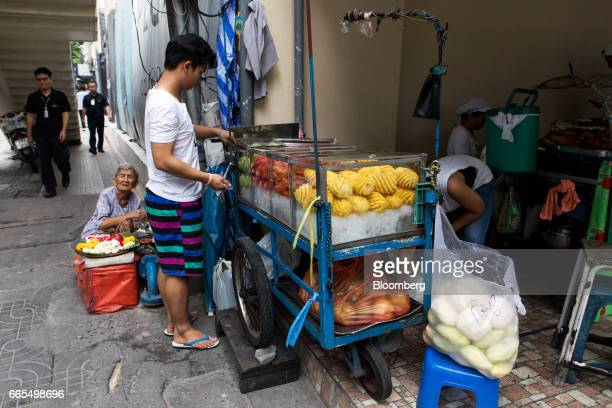 Vendors stand at a street cart selling fresh fruit in the Phaya Thai District of Bangkok Thailand on Wednesday April 5 2017 The central...