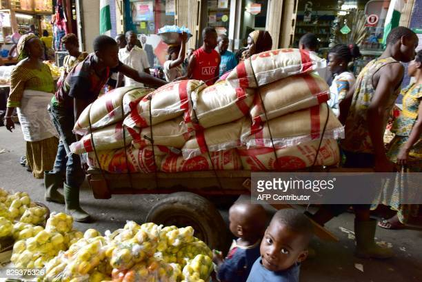 Vendors transport bags of rice at the large market of Adjame a popular district of Abidjan on August 10 2017 The Ivorian government in a council of...