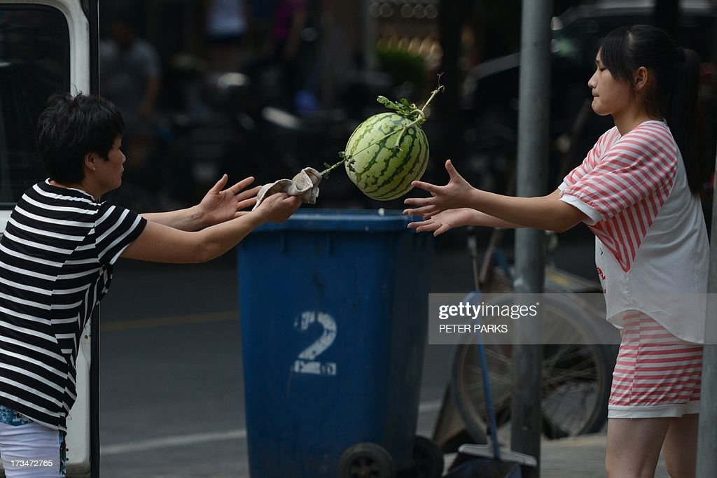 Vendors unload watermelons outside a market in Shanghai on July 15, 2013. China's gross domestic product expanded 7.5 percent in the April-June quarter, official data showed, a second consecutive slowdown in growth as worries mount over the health of the world's number two economy. AFP PHOTO/Peter PARKS