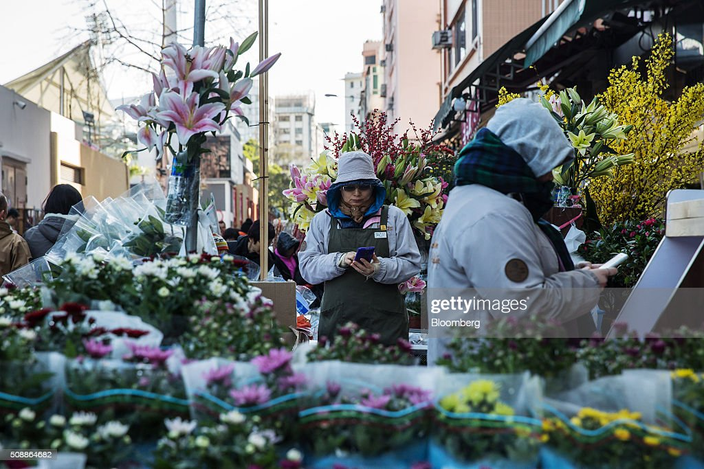 Vendors use smartphones near flowers displayed for sale for the Lunar New Year at a flower market in the Mong Kok district of Hong Kong, China, on Sunday, Feb 7, 2016. The city's financial markets will close on Feb. 8 for the Lunar New Year holidays and resume trading on Feb. 11. Photographer: Billy H.C. Kwok/Bloomberg via Getty Images