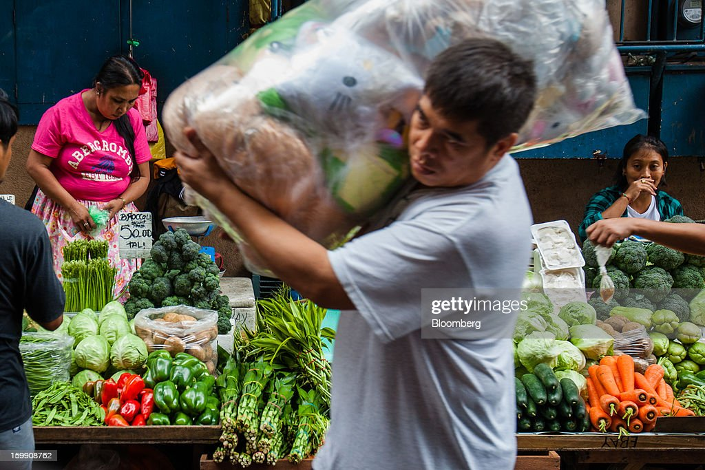 Vendors wait for customers at their vegetable stalls as a man walks past carrying a bag of goods at the Divisoria market in Manila, the Philippines, on Tuesday, Jan. 22, 2013. Philippine government bonds advanced on speculation the central bank will hold its benchmark interest rate at a record low at a meeting tomorrow, supporting demand for the nation's debt. Photographer: Julian Abram Wainwright/Bloomberg via Getty Images