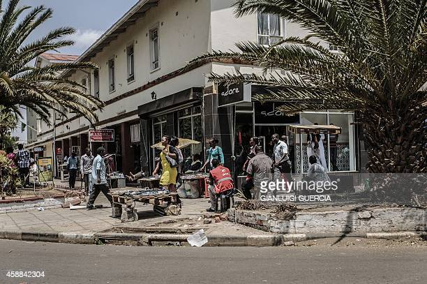 Vendors wait for customers on a sidewalk in the central Lusaka Businness district on November 12 a day after the burial of the late Zambian president...