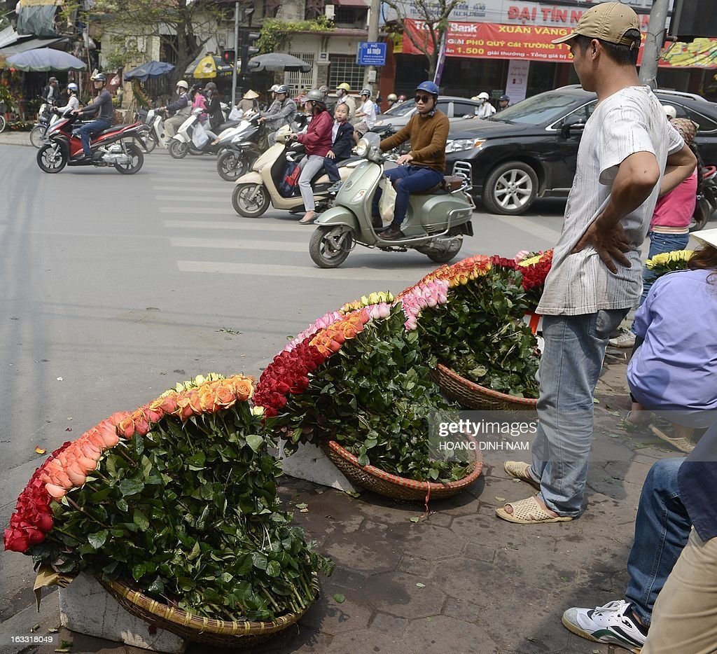 Vendors wait with their roses at a street corner as Vietnamese celebrate the International Women's Day in Hanoi on March 8, 2013. The day is a good business opportunity for florists with a sharp rise of flowers's prices, especially for roses. AFP PHOTO/HOANG DINH Nam