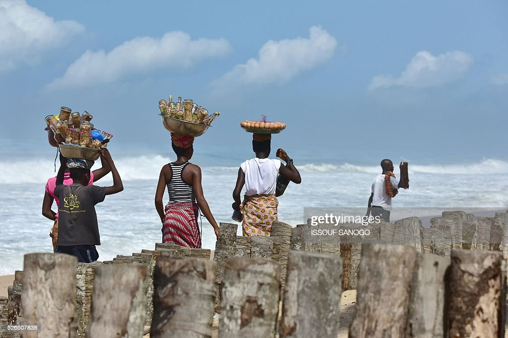Vendors walk on the Grand Bassam beach on April 30, 2016 where 19 people were killed during a jihadist attack on March 13. France will increase the number of its troops in Ivory Coast, Defence Minister Jean-Yves Le Drian said on April 29 on a trip to the African nation which hosts a regional base for French forces. / AFP / ISSOUF