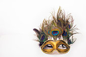Venetian carnival mask with peacock feathers on white background