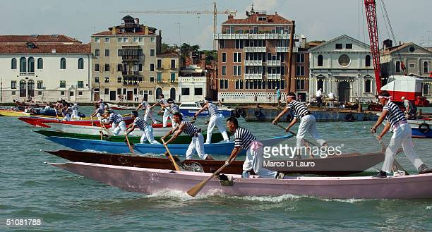 Venetian gondoliers participate in a rowing competition to celebrate the Festa del Redentore July 18 2004 in Venice Italy This festival is second...