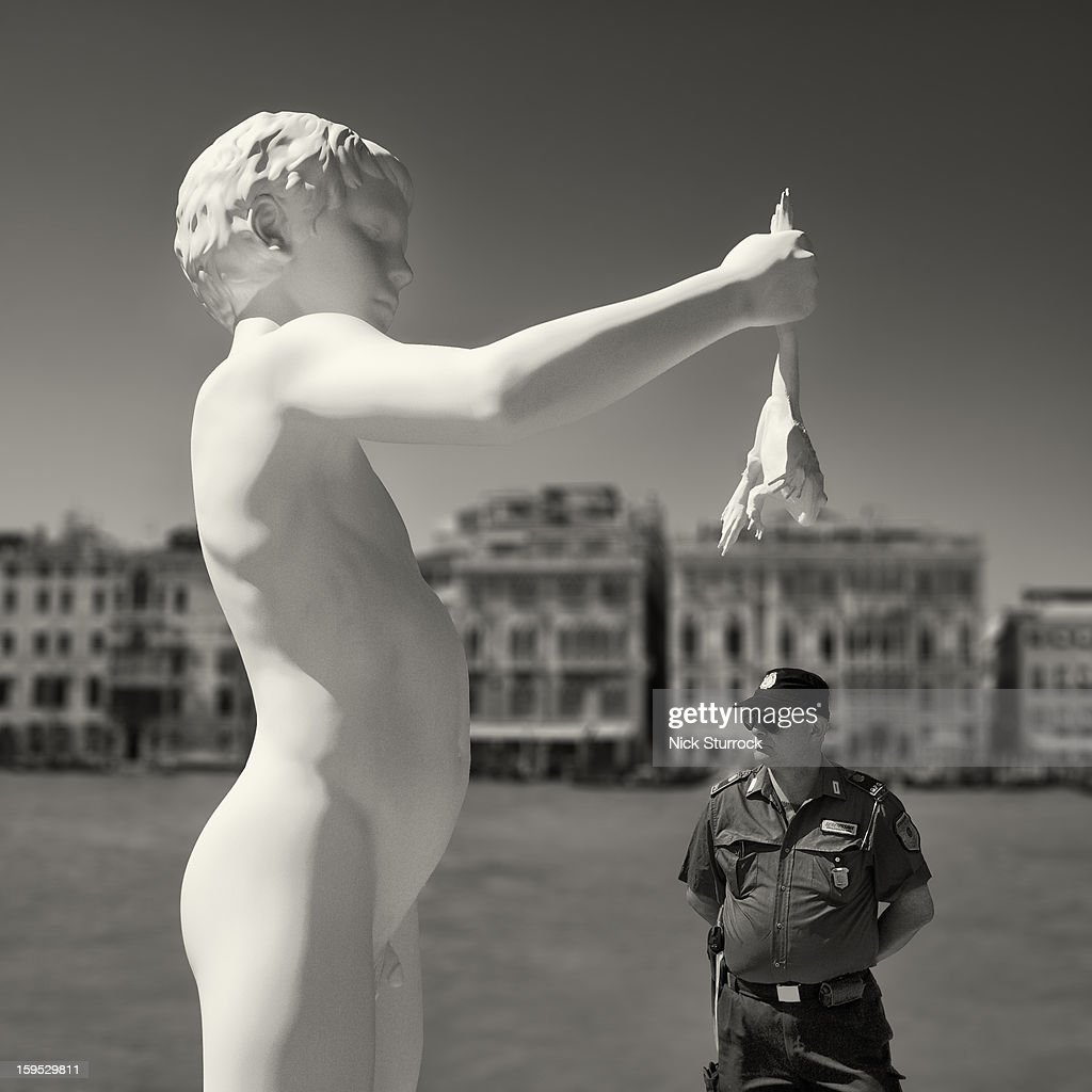 Venetian policeman patrols beneath a giant statue of a boy holding a frog, on the banks of the Gran Canal