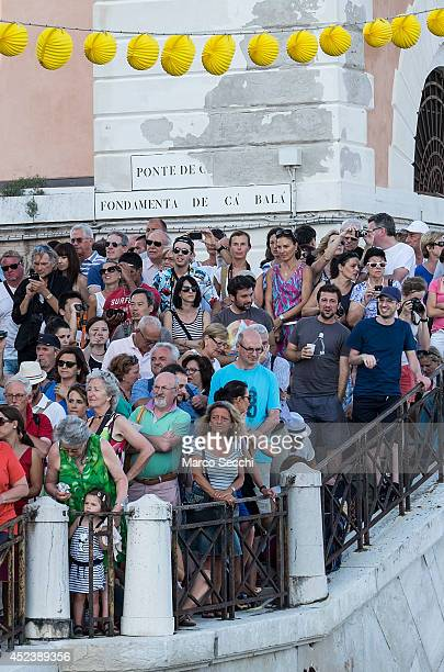 Venetians and Tourist watch from the bank of Giudecca Canal the opening of the votive bridge to the Redentore Church on July 19 2014 in Venice Italy...