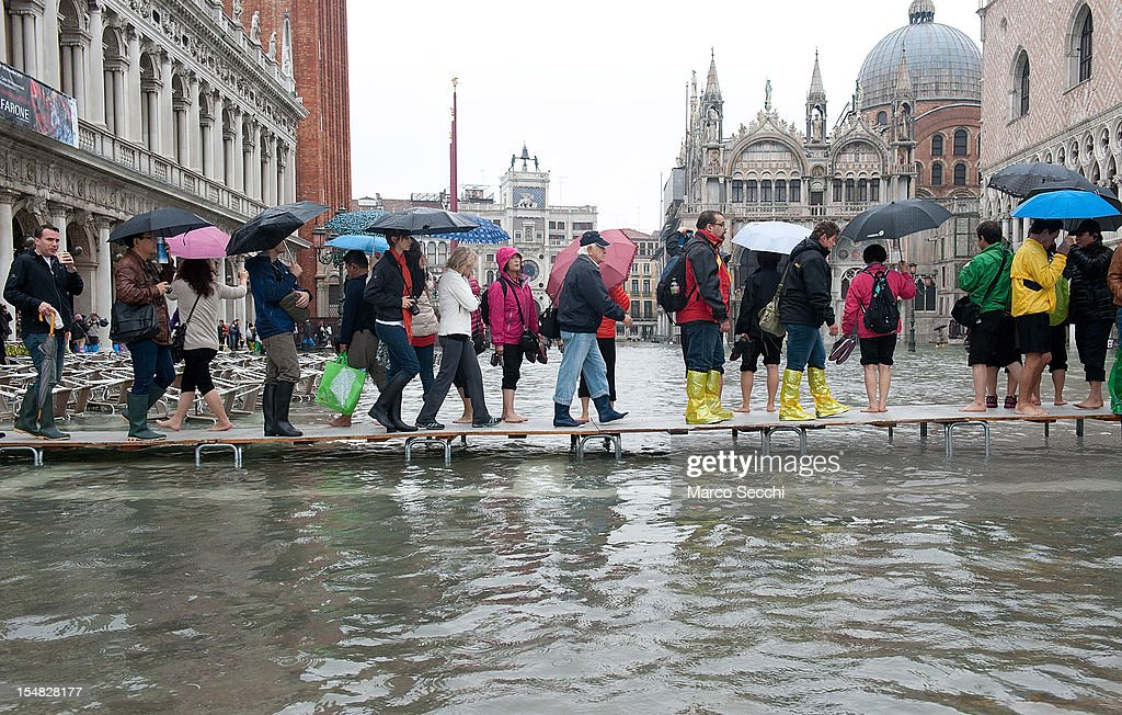 Venetians and tourists use the walkways in front of St Mar's Basilica during a high tide on October 27, 2012 in Venice, Italy. The high tide, or acqua alta as it is locally known, stood at 127 centimeters this morning.