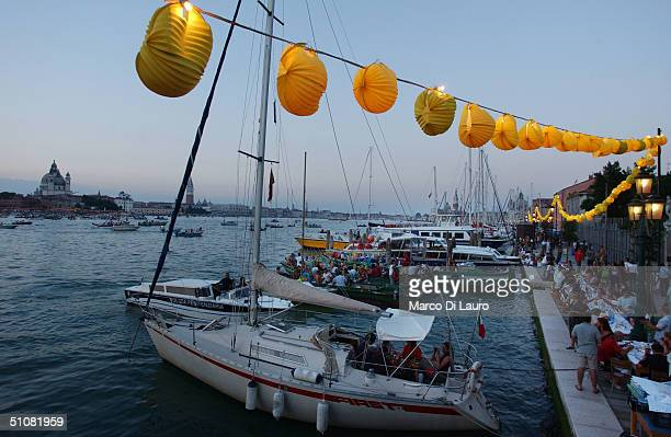 Venetians have dinner on their boats as they wait for the fireworks in the lagoon to celebrate during the Festa del Redentore in Venice July 17...