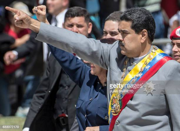 TOPSHOT Venezelan President Nicolas Maduro and first lady Cilia Flores greet supporters at the start of a military parade in Caracas on February 1...
