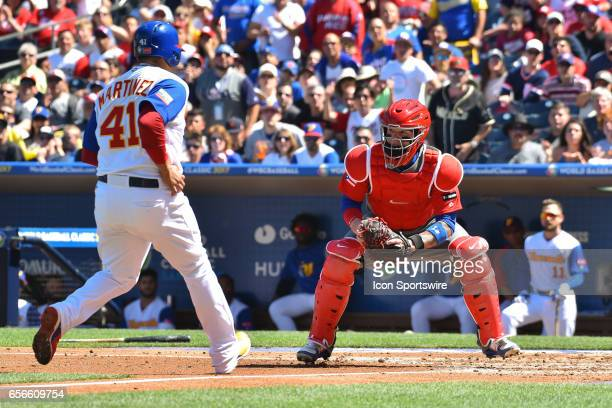 Venezuela Designated Hitter Victor Martinez tries to score on a fly ball as Puerto Rico Catcher Roberto Perez gets ready to apply the tag during the...