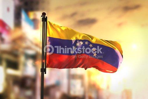Bandera de Venezuela contra la ciudad borrosa de fondo en contraluz amanecer : Foto de stock