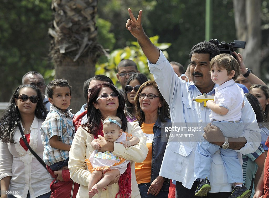 Venezuelan acting President and presidential candidate Nicolas Maduro (R) gestures outside of a polling station with his grandson before casting his vote in Caracas, on April 14, 2013. Venezuelans flocked to the polls Sunday to vote for Hugo Chavez's successor, choosing between the handpicked heir of his socialist revolution and an opponent vowing change in the divided nation.