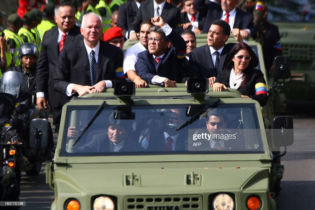 Venezuelan Acting President Nicolas Maduro (driving), Bolivian President Evo Morales (beside him), President of the Legislative Assembly, Diosdado Cabello (back-L), PDVSA president and Minister of Oil, Mines and Energy Rafael Ramirez (back-2L), Foreign Minister Elias Jauja (C) and Maduro's wife Cilia Flores (back-R) follow aboard a military vehicle the coffin with the remains of late Venezuelan President Hugo Chavez as it is taken from the Military Academy to former 4 de Febrero barracks in Caracas, on March 15, 2013. The body of Chavez was moved Friday to the barracks in a final march to honor of the leftist leader a month before elections are held to pick his successor. The Caracas military academy, where Chavez's casket has been on view, served as the starting point for the procession escorting the remains of the 58-year-old, who last week succumbed to cancer after 14 years in power. AFP PHOTO/GERALDO CASO