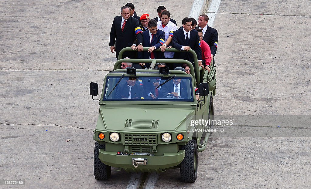 Venezuelan acting President Nicolas Maduro (driving), Bolivian President Evo Morales (beside him), the President of the Legislative Assembly, Diosdado Cabello (back-L), PDVSA president Rafael Ramirez (sitting behind Morales), Foreign Minister Elias Jauja (standing C) and other authorities ride a military vehicle following the hearse with the remains of late Venezuelan President Hugo Chavez as it is taken to his resting place at the former '4 de Febrero' barracks in Caracas, on March 15, 2013. Hundreds of thousands of Venezuelans thronged the streets of Caracas on Friday to bid a final farewell to the late leader a month before elections to pick his successor. The Caracas military academy, where Chavez's casket has been on view, served as the starting point for the procession escorting the remains of the 58-year-old, who last week succumbed to cancer after 14 years in power. AFP PHOTO/JUAN BARRETO