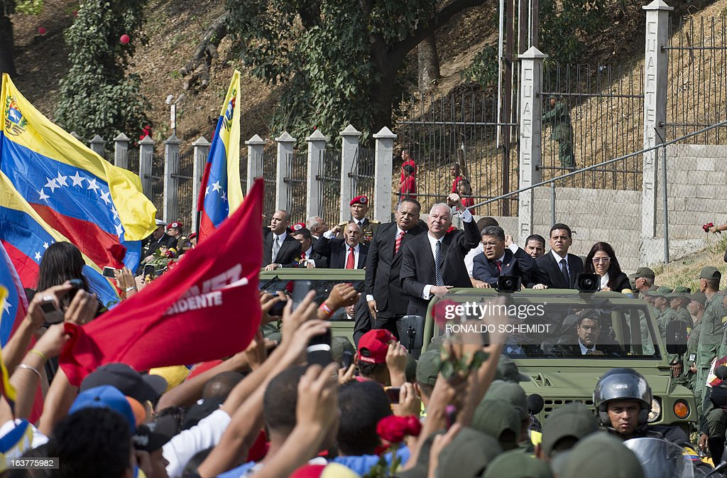 Venezuelan Acting President Nicolas Maduro (driving), Bolivian President Evo Morales (beside him), President of the Legislative Assembly, Diosdado Cabello (back-L), PDVSA president and Minister of Oil, Mines and Energy Rafael Ramirez (back-2L), Foreign Minister Elias Jauja (C) and Maduro's wife Cilia Flores (back-R) among other authorities ride a military vehicle following the hearse with the remains of late Venezuelan President Hugo Chavez as it is taken to his resting place at the former '4 de Febrero' barracks in Caracas, on March 15, 2013. Hundreds of thousands of Venezuelans thronged the streets of Caracas on Friday to bid a final farewell to the late leader a month before elections to pick his successor. The Caracas military academy, where Chavez's casket has been on view, served as the starting point for the procession escorting the remains of the 58-year-old, who last week succumbed to cancer after 14 years in power.