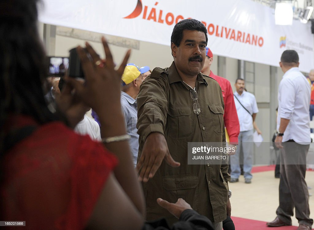 Venezuelan acting president Nicolas Maduro greets a supporter upon arrival for a working session in Caracas on April 1st, 2013. Venezuela will hold presidential elections on April 14, 2013. AFP PHOTO/JUAN BARRETO
