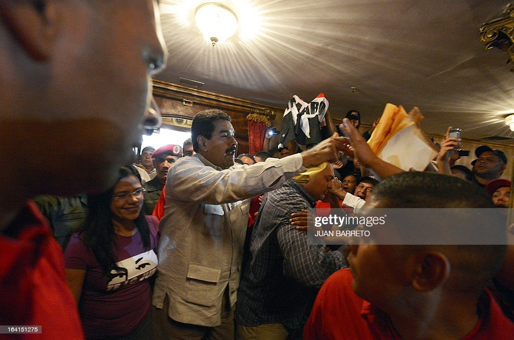Venezuelan acting president Nicolas Maduro (C) greets supporters before a rally with leftist political parties in Caracas on March 20, 2013. Maduro, who succeeded the late Hugo Chavez as Venezuela's interim president, has an 18 point lead over the opposition's Henrique Capriles ahead of mid-April elections, a polling firm said Tuesday. AFP PHOTO/JUAN BARRETO