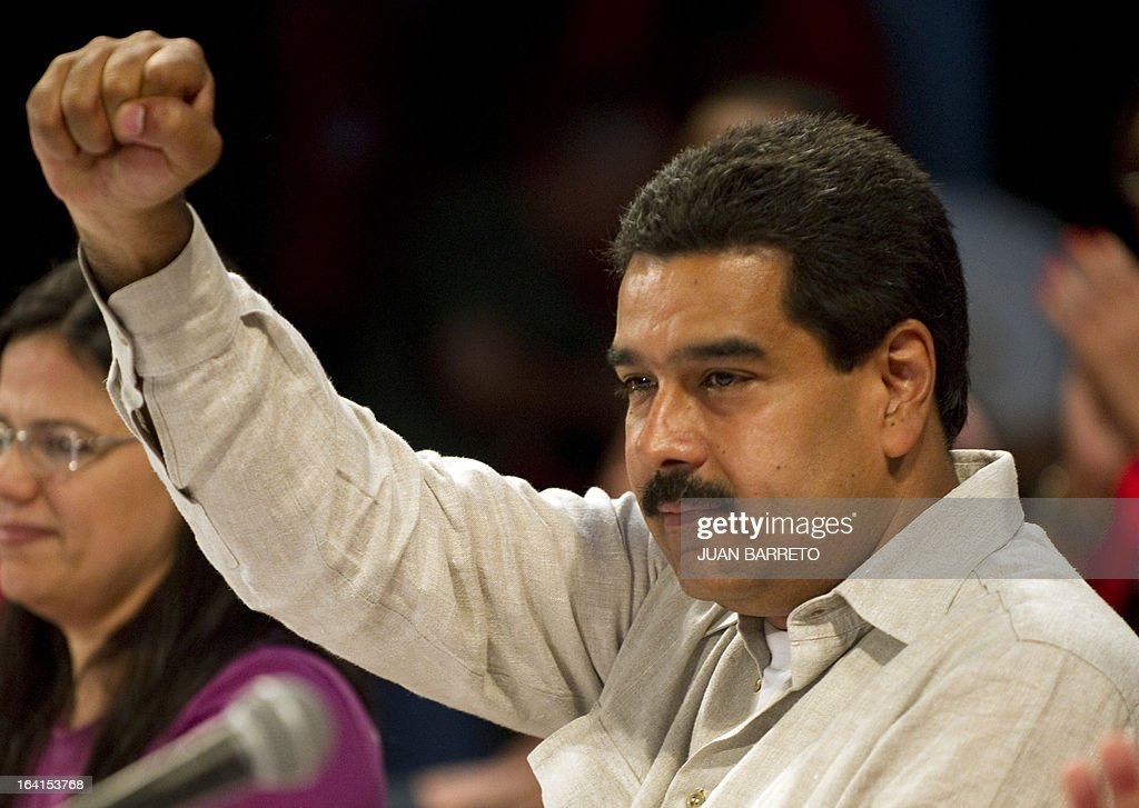Venezuelan acting president Nicolas Maduro raises his clenched fist during a rally with leftist political parties in Caracas on March 20, 2013. Maduro, who succeeded the late Hugo Chavez as Venezuela's interim president, has an 18 point lead over the opposition's Henrique Capriles ahead of mid-April elections, a polling firm said Tuesday.