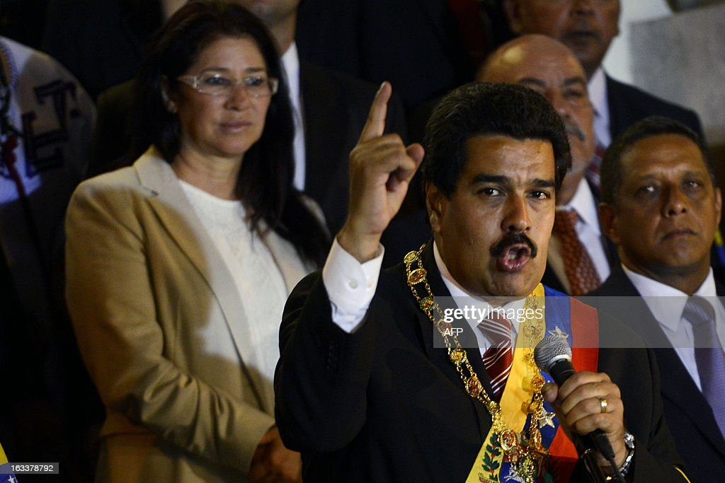 Venezuelan acting president Nicolas Maduro (C) speaks during the ceremony in which he was sworn in, next to his wife Cilia Flores (L) on March 8, 2013, in Caracas. Hugo Chavez's handpicked successor, Nicolas Maduro, was sworn in as acting president of Venezuela late Friday in a disputed inauguration boycotted by the main opposition group. AFP PHOTO/ LEO RAMIREZ