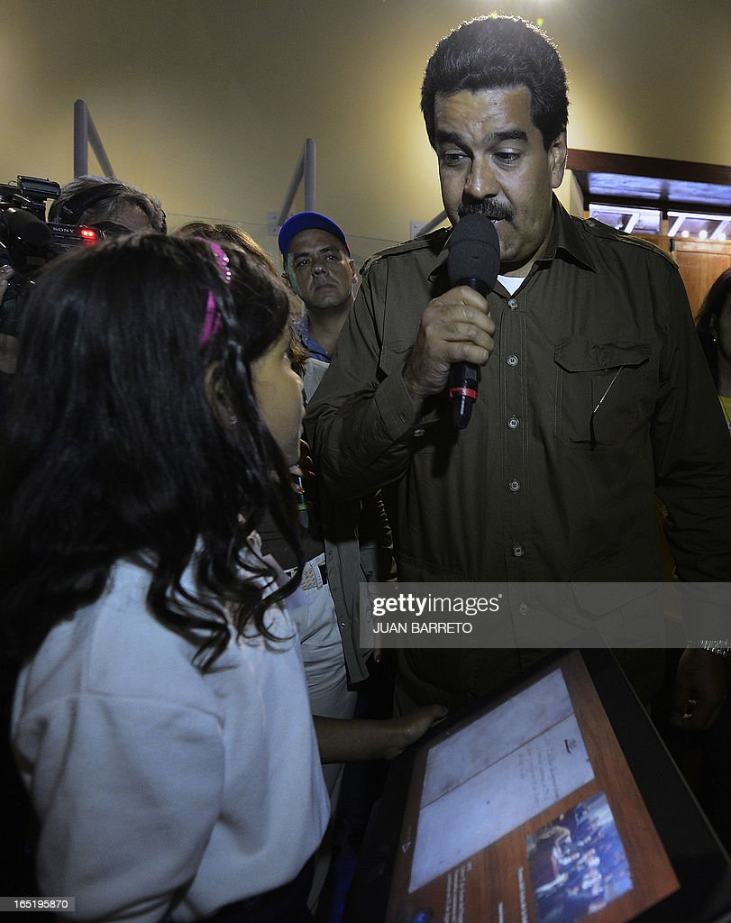 Venezuelan acting president Nicolas Maduro (R) speaks with a girl during a visit to a museum in Caracas on April 1st, 2013. Venezuela will hold presidential elections on April 14, 2013. AFP PHOTO