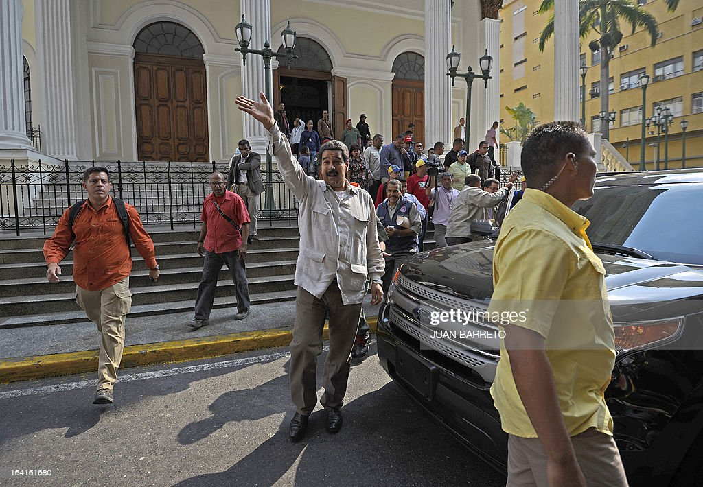 Venezuelan acting president Nicolas Maduro (C) waves at the end of a rally with leftist political parties in Caracas on March 20, 2013. Maduro, who succeeded the late Hugo Chavez as Venezuela's interim president, has an 18 point lead over the opposition's Henrique Capriles ahead of mid-April elections, a polling firm said Tuesday. AFP PHOTO/JUAN BARRETO