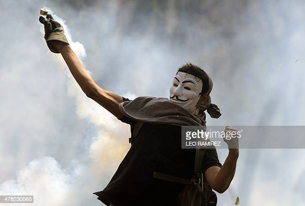 A Venezuelan activist wearing a Guy Fawkes mask returns a tear gas bomb to riot police during a protest against the government of President Nicolas...