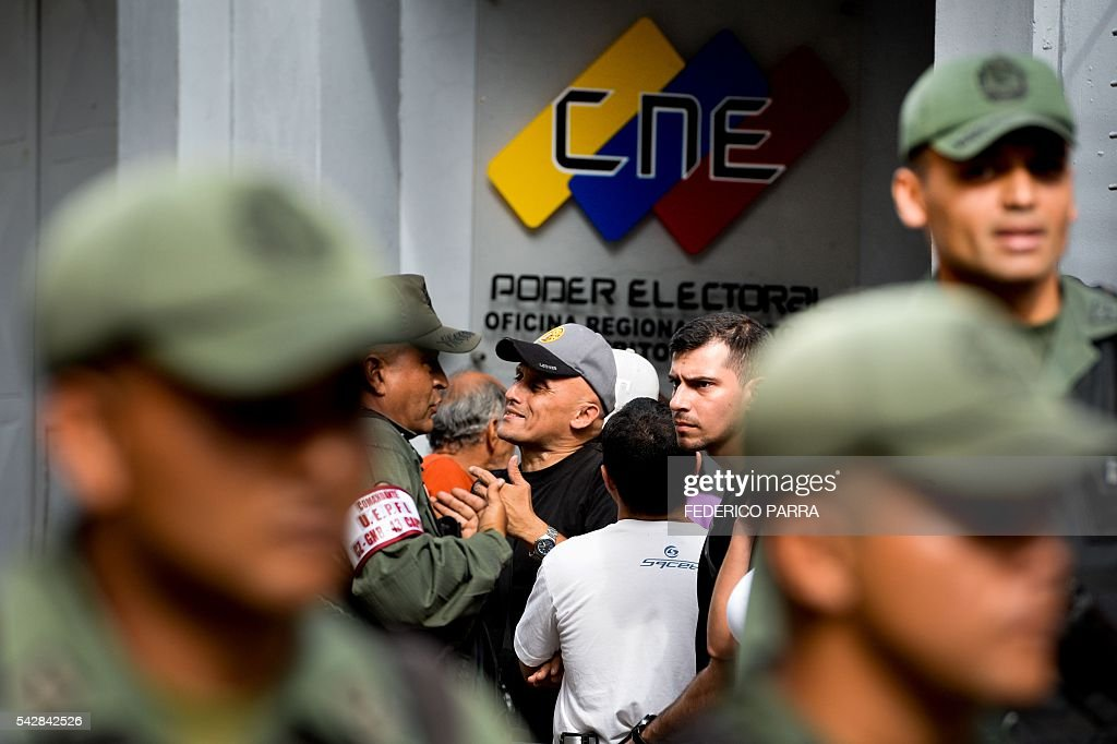 A Venezuelan (C) argues with members of the national police during a spontaneous demonstration after the closure of centres to authenticate their signatures for a recall referendum against Venezuelan President Nicolas Maduro, in front of the National Electoral Council (CNE) in Caracas, on June 24, 2016. Soaring crime, runaway inflation and a sharply contracting economy, worsened by falling oil prices, have fueled a drive for a recall referendum to remove Maduro, as a way out of the crisis. / AFP / FEDERICO