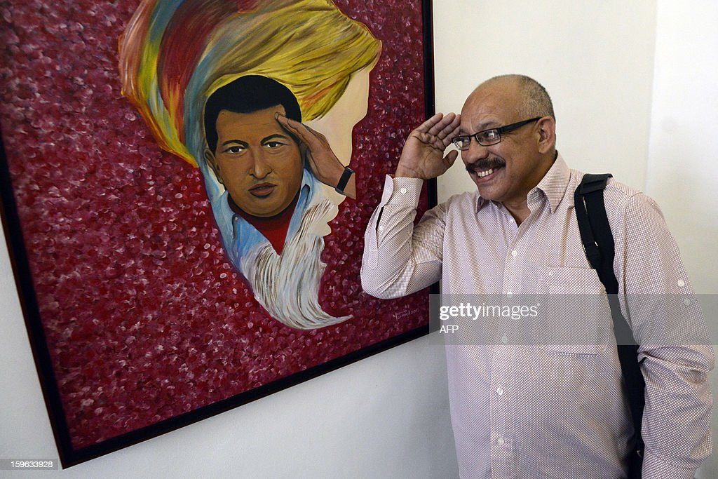Venezuelan artist Mervin Marmol salutes his painting at the exhibition on Venezuelan President Hugo Chavez titled 'Chavez Vive y Vencera' (Chavez Lives and Will Overcome), in Caracas on January 17, 2013. Chavez remains gravely ill in a Havana hospital some five weeks after complications arose during his fourth round of cancer surgery. AFP PHOTO/Leo RAMIREZ