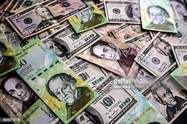 Venezuelan bolivar notes and various denominations of US dollar bills are arranged for a photograph in Caracas Venezuela on Sunday Feb 22 2015 A...