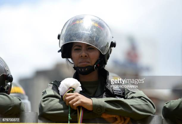 A Venezuelan Bolivarian National Guard member holds a flower during a women's march aimed to keep pressure on President Nicolas Maduro whose...