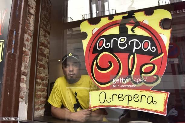 Venezuelan businessman Edgar Rodriguez poses inside his restaurant called 'Arepa Ole' in Madrid on June 14 2017 Edgar Rodriguez landed in Madrid ten...