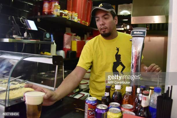 Venezuelan businessman Edgar Rodriguez serves a beer in his restaurant called 'Arepa Ole' in Madrid on June 14 2017 Edgar Rodriguez landed in Madrid...