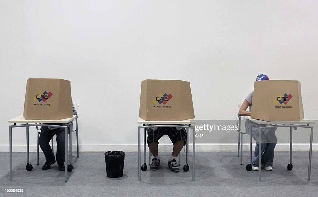 Venezuelan citizens living in Spain choose their ballots before casting their vote for Venezuela's presidential election at a polling station in Santa Cruz de Tenerife on the Spanish Canary island of Tenerife on April 14, 2012. Venezuelans headed to the polls to elect Hugo Chavez's successor, with his political heir, Nicolas Maduro, hoping to continue his socialist revolution and rival Henrique Capriles vowing change in the divided nation. AFP PHOTO / DESIREE MARTIN