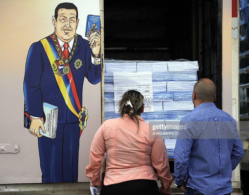 Venezuelan Constitutions with drawings depicting late President Hugo Chavez, are delivered at a school in Caracas, on September 16, 2013. AFP PHOTO/JUAN BARRETO