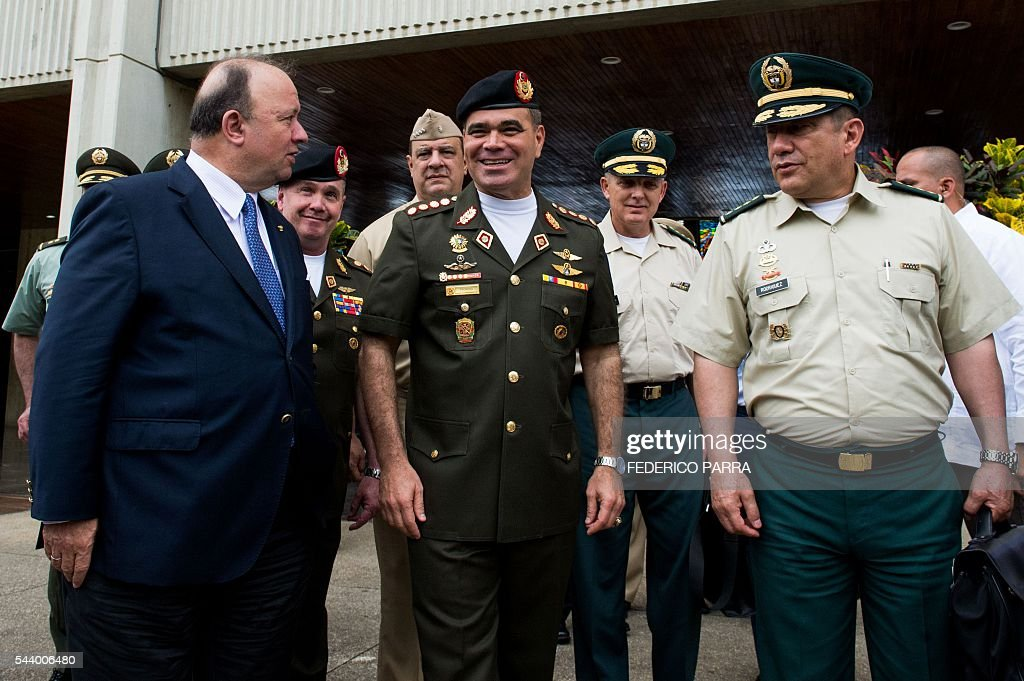 Venezuelan Defence Minister Padrino Lopez (C) welcomes his Colombian counterpart Luis Carlos Villegas (L) upon the latter's arrival for a meeting at the Defence Ministry in Caracas on June 30, 2016. / AFP / FEDERICO