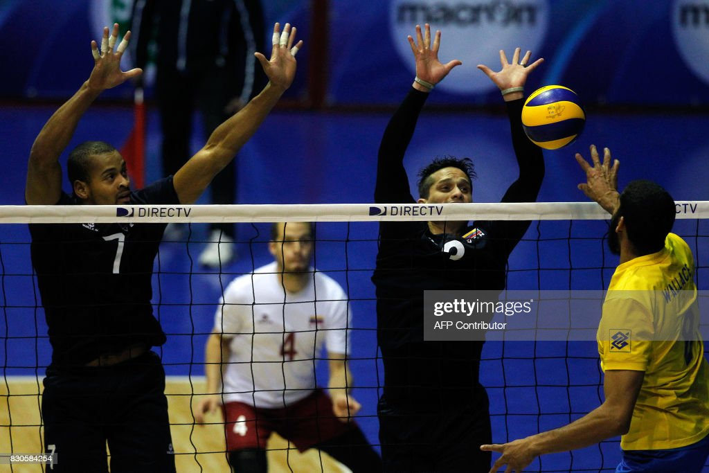 Venezuelan Edson Valencia (L) and Fernando Gonzalez (R) try to block Brazilian Wallace Souza, during their Men's South American Volleyball Championship final in Santiago, on August 11, 2017. /