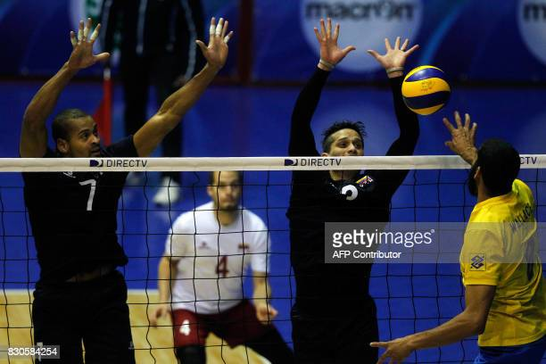 Venezuelan Edson Valencia and Fernando Gonzalez try to block Brazilian Wallace Souza during their Men's South American Volleyball Championship final...