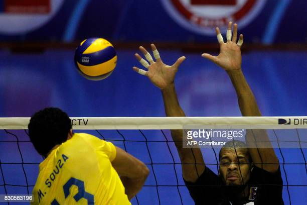 Venezuelan Edson Valencia tries to block the smash by Brazilian Mauricio Souza during their Men's South American Volleyball Championship final in...