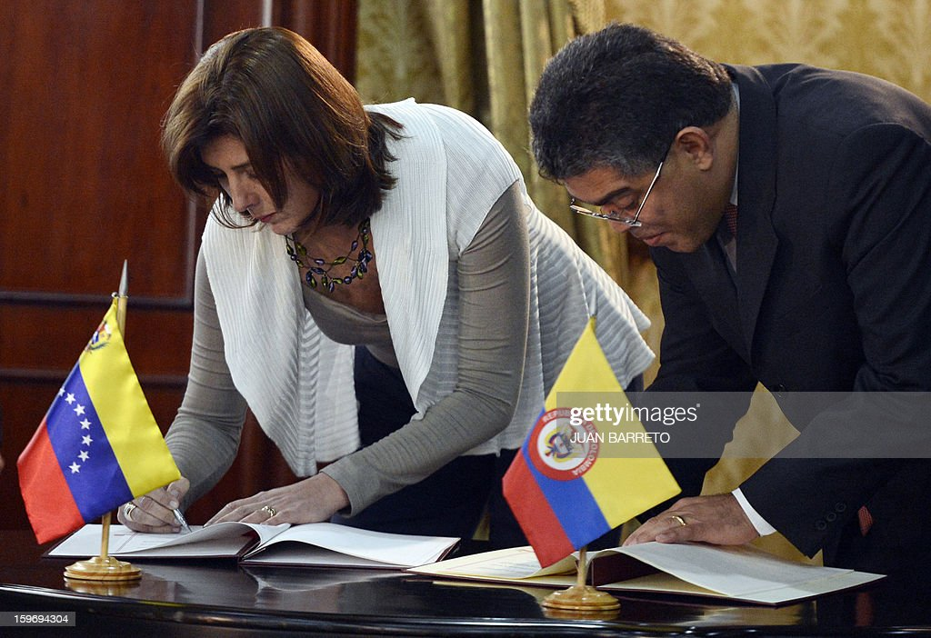 Venezuelan Foreign Minister Elias Jaua(R) and Colombian Foreign Minister Maria Angela Holguin (L) sign agreements during a meeting in Caracas on January 18, 2013. AFP PHOTO/JUAN BARRETO