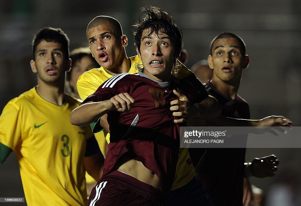Venezuelan forward Jose Romo (C) fights for the ball with Brazilian defender Doria (C-L) during their South American U-20 Championship Group B football match, at Bicentenario stadium in San Juan, Argentina, on January 16, 2013. Four South American teams will qualify for the FIFA U-20 World Cup Turkey 2013. Brazil won by 1-0.